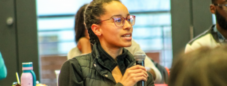 Graduate student speaking into microphone