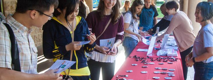 students gathered around a long red information table