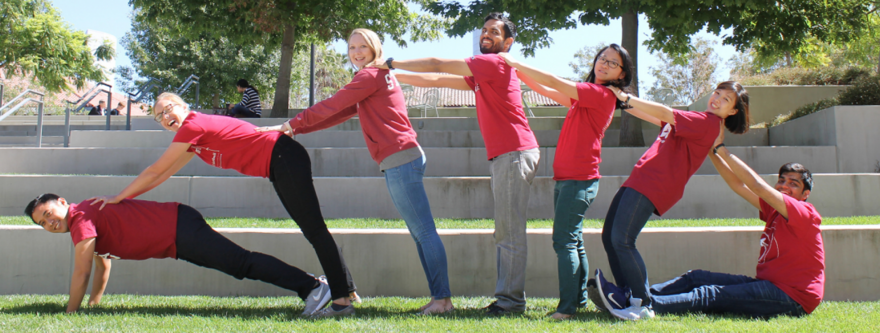 A photo of seven students arrayed in the shape of a semi-circle in red shirts and jeans.