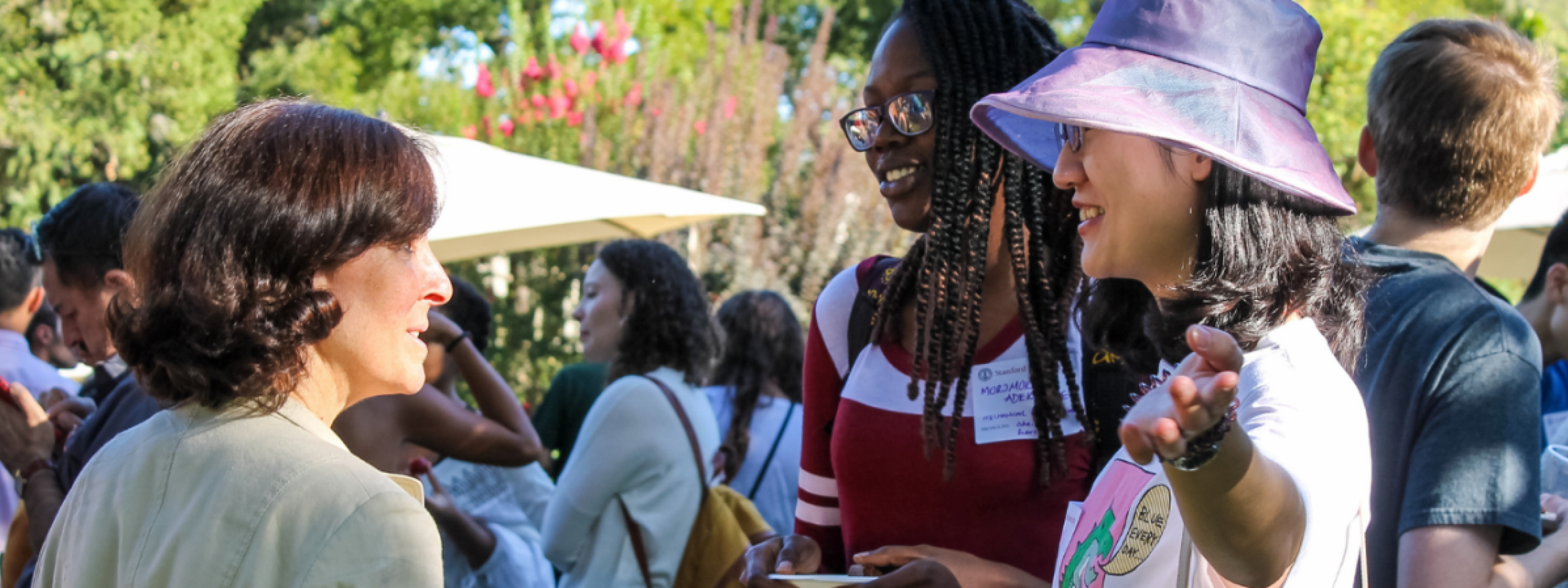 Stacey F. Bent talks to two graduate students at an outdoor reception