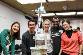 A group of students smiling with their finished project.