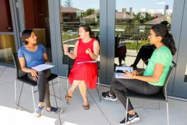 Three Stanford grad students engaged in a discussion