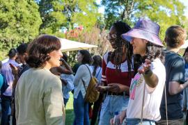 Stacey Bent talking to two graduate students at an outdoor reception.
