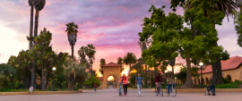 a pink and purple sky in the main quad, with people walking bikes in the foreground