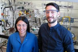 Aisulu Aitbekova and Matteo Cargnello wear safety goggles and stand in front of intricate lab equipment