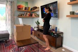 Anjali Bisaria stands in front of a TV screen and a laptop on a cardboard box, presenting her PhD defense