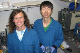 David Mackanic and Zhiao Yu stand in their lab, holding a dish with small silver batteries