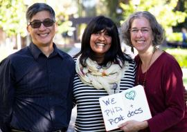 "Three people pose for a photo with a handwritten sign that says ""We [heart symbol] PhDs and Postdocs"""
