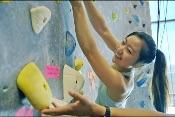 screenshot of a person with a ponytail climbing on a climbing wall