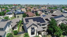 aerial image of two-story houses in a neighborhood with solar panels on the roofs