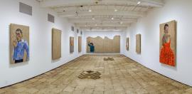an art exhibit with paintings on adboe along the walls, and a brick or stone floor
