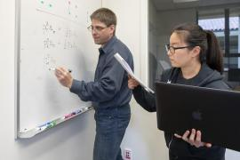 a woman in glasses holds a laptop and looks at a paper while a man with glasses writes on a whiteboard