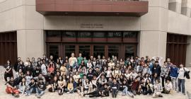 a large group of grad students and high schoolers pose for a group photo in front of a building