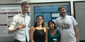 four people stand in front of a poster presentation. The person on the left has his thumb up