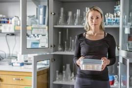 Joy Franco stands in front of an open cabinet in a lab and holds a plastic tub
