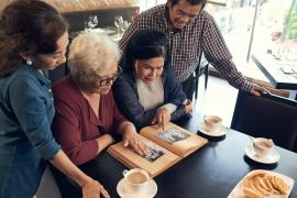 Four older adults gather around a table and look at a photo album