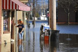 a person wades through shin-height water near a shop in Annapolis, Maryland