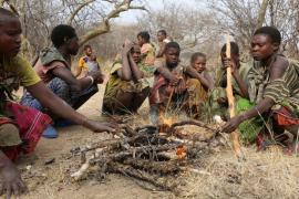 a group of members of the Hazda population in Tanzania, around a fire