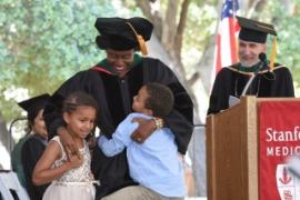 A person in doctoral graduation robe stands on stage hugging two children