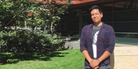 Photo of Eddy Albarran, standing and smiling in front of a green space outside of a building at Stanford