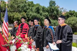 6 people in doctoral robes stand behind flowers and an American flag