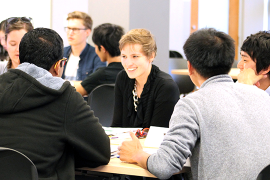 students smiling at a table