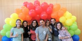 seven students post under a rainbow balloon arch at the Stanford School of Medicine's first LGBTQ+ Forum