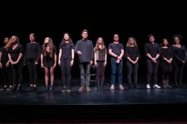 A diverse group of students wearing all black stand on a dark theater stage