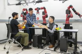 three males sit at a table with a red robotic arm
