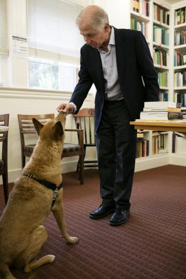A man in a suit stands and gives a dog a treat