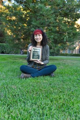 Sandra Schachat holding a previous award from the Entomological Society of America