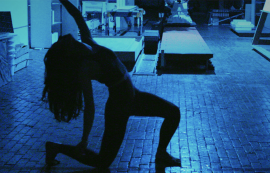 silhouette of someone kneeling on the ground with one arm towards the sky. The light in the background is blue