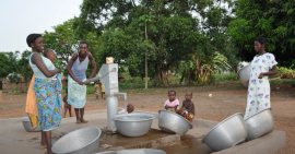 Women and their children fill buckets of water