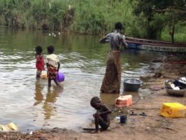 A woman bathes at a riverbank, while three children play nearby