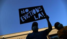 """A masked person holds a """"No Eviction LA!"""" Sign"""