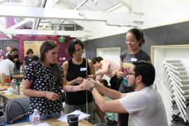 four students gathering around a project involving two long sticks taped together