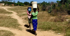 two people walking on a dirt road, carrying water buckets on their heads