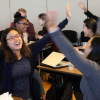 students raise their arms during a joyous, interactive activity